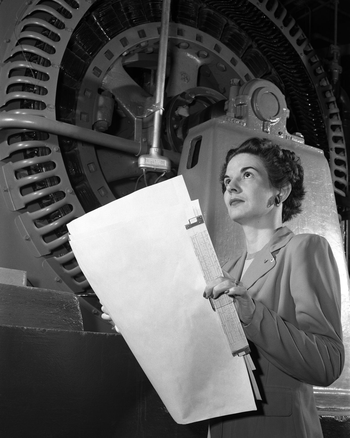 image of woman looking up, carrying plans and slide rule, with huge machinery in the background