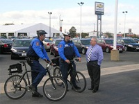 Bike Cops Speaking to Man at Car Dealership