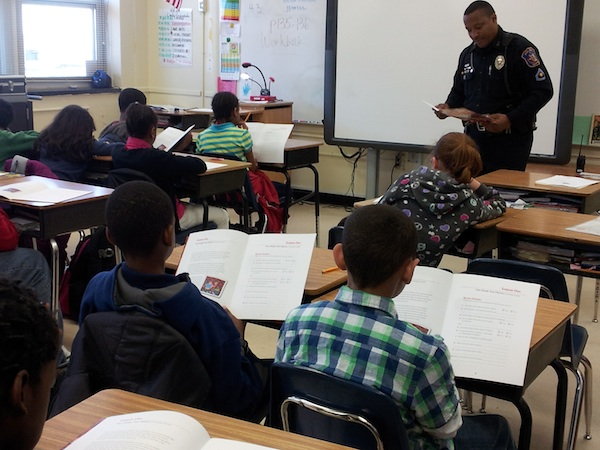 Officer Standing at the Front of a Classroom - Students Seated at Desks